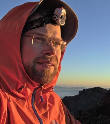 Self-portrait on the summit of Kengamine Peak. Note sun reflections on glasses & headlamp