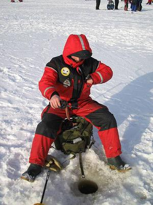 A gentleman ice fishing in Canada